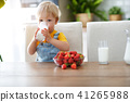 happy baby boy eating strawberries with milk 41265988