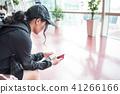 공항 출국장에서 여권을 보면서 탑승 시간을 기다리는 젊은 여자. 41266166