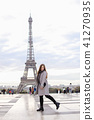 Caucasian woman in grey coat standing near Eiffel Tower in Paris. 41270935