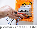 Electrician at work on an electrical panel 41283369