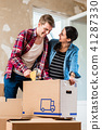 Young man and his girlfriend sealing a box while renovating their home 41287330