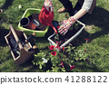 Watering planted red flowers 41288122