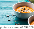 Creamy pumpkin soup in white bowls 41292626