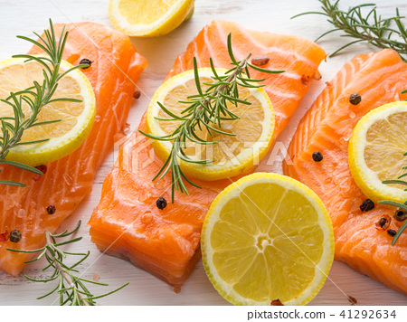 Raw salmon on wooden board with herbs 41292634