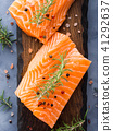 Raw salmon on wooden board with herbs 41292637
