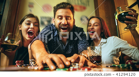 Side view photo of friends sitting at wooden table. Friends having fun while playing board game. 41294120
