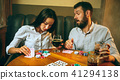 Side view photo of friends sitting at wooden table. Friends having fun while playing board game. 41294138