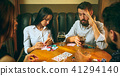 Side view photo of friends sitting at wooden table. Friends having fun while playing board game. 41294140