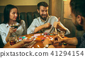 Side view photo of friends sitting at wooden table. Friends having fun while playing board game. 41294154