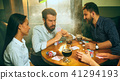 Side view photo of friends sitting at wooden table. Friends having fun while playing board game. 41294193