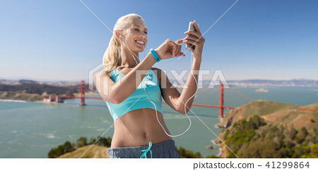 woman with smartphone and earphones doing sports 41299864