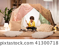 boy with pots playing music in kids tent at home 41300718