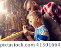 father and son with ruler measure wood at workshop 41301664
