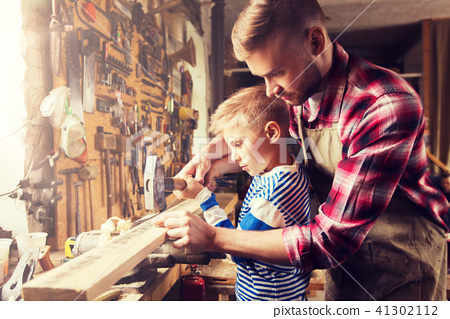 father and son with hammer working at workshop 41302112