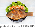fried fish with vegetable on black dish. top view 41307185