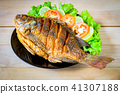 fried fish with vegetable on black dish. top view 41307188
