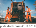 Two refuse collection workers loading garbage into waste truck 41312218