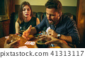 Friends sitting at wooden table. Friends having fun while playing board game. 41313117