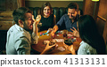 Side view photo of friends sitting at wooden table. Friends having fun while playing board game. 41313131