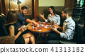 Side view photo of friends sitting at wooden table. Friends having fun while playing board game. 41313182
