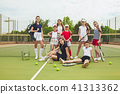 Portrait of group of girls as tennis players holding tennis racket against green grass of outdoor 41313362