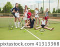 Portrait of group of girls as tennis players holding tennis racket against green grass of outdoor 41313368