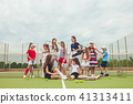 Portrait of group of girls as tennis players holding tennis racket against green grass of outdoor 41313411