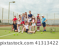 Portrait of group of girls as tennis players holding tennis racket against green grass of outdoor 41313422