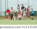 Portrait of group of girls as tennis players holding tennis racket against green grass of outdoor 41313528