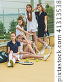 Portrait of group of girls as tennis players holding tennis racket against green grass of outdoor 41313538