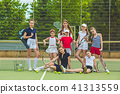 Portrait of group of girls as tennis players holding tennis racket against green grass of outdoor 41313559