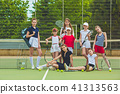 Portrait of group of girls as tennis players holding tennis racket against green grass of outdoor 41313563