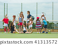 Portrait of group of girls as tennis players holding tennis racket against green grass of outdoor 41313572