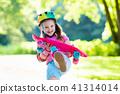 Child riding skateboard in summer park 41314014