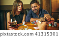 Friends sitting at wooden table. Friends having fun while playing board game. 41315301