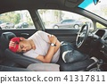 Tired young man driving his car. sleeping inside h 41317811