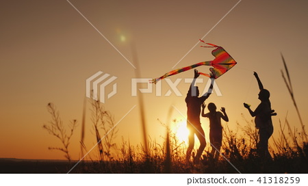 Happy family playing with a kite at sunset. Mom, Dad and daughter are happy together 41318259