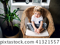 A toddler boy sitting on the wicker chair in the bathroom at home. 41321557