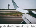 Wing of an aircraft open trailing edge flaps during landing. Airport Tower in background 41326347
