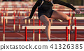 High school girls running a hurdles race 41326385