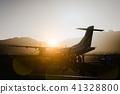 Passengers boarding to propeller aircraft on dusty morning. Mountain range surrounding runway on Sao 41328800