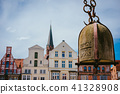 Weight of old Crane hanging in front of facade of historical buildings in Harbor Lueneburg, Lower 41328908
