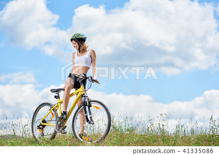 Young Happy Woman Riding Bicycle In The Mountains At Summer