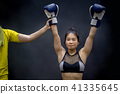 Referee lifting female boxer hand, winner of match 41335645