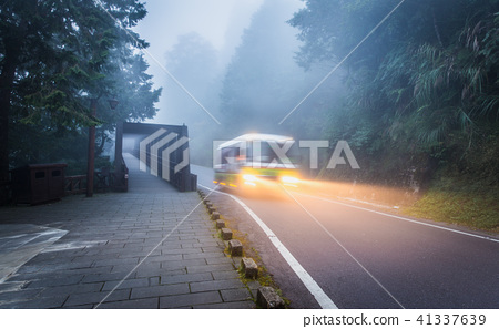 Running bus on local road inside tropical forest 41337639