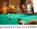 Young men and women playing billiards at office after work. 41339980