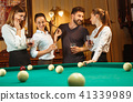 Young men and women playing billiards at office after work. 41339989