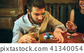 Side view photo of friends sitting at wooden table. Friends having fun while playing board game. 41340054