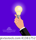 The hand of the businessman holds the shining bulb 41361752