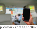 Hand holding mobile phone in back seat of car 41367842
